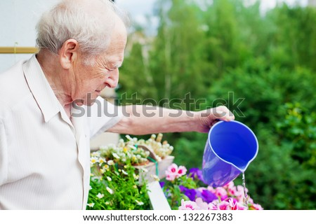 serious senior man watering the flowers on his balcony - stock photo