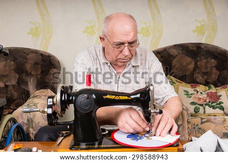 Serious Senior Man Wearing Eyeglasses Working on Needle Point Wall Hanging Craft Using Old Fashioned Sewing Machine at Home in Living Room - stock photo