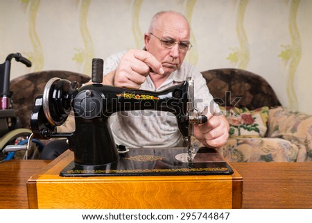 Serious Senior Tailor Man with Bald Head, Putting Thread on his Manual Sewing Machine Inside his House. - stock photo