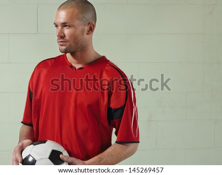 Serious soccer player holding ball against green wall - stock photo