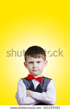 Serious,Stubborn,sad,upset  little boy,child  isolated over yellow background.Facial expression - stock photo