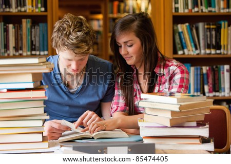 Serious students looking at a book in a library - stock photo