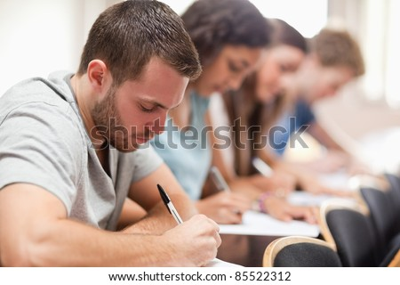 Serious students sitting for an examination in an amphitheater - stock photo