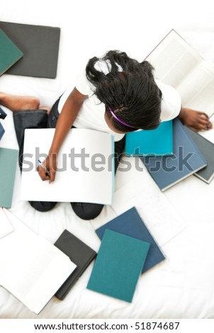 Serious teen girl studying sitting on her bed at home - stock photo
