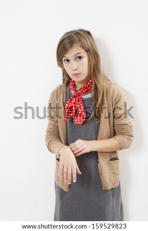 serious teen girl wearing knitted  beige jacket and red in spot kerchief - stock photo
