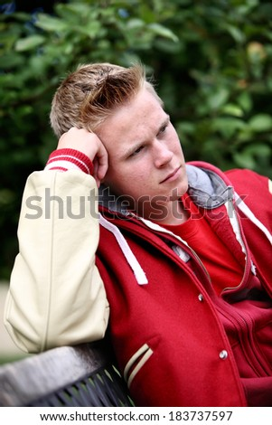 Serious teenage boy sitting on a bench outdoors - stock photo