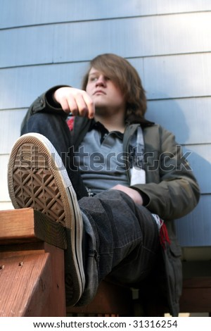 Serious teenage boy sitting on a railing outdoors in winter, from perspective of subject's feet.  Foot is main focus with shallow depth of field. - stock photo