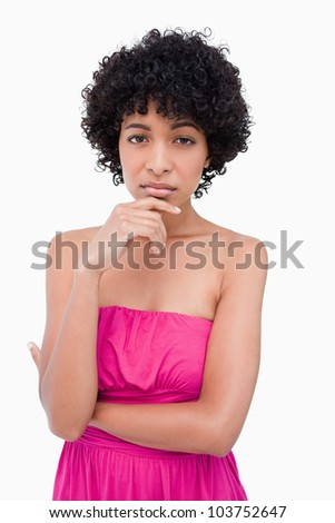 Serious teenage placing hand on chin while looking ahead - stock photo