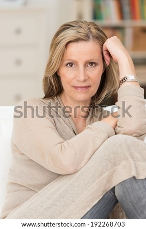 Serious thoughtful middle-aged woman sitting with her knees up on a sofa staring directly at the camera - stock photo