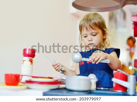 serious toddler girl is playing - stock photo