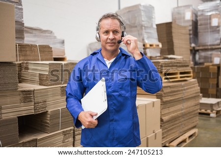 Serious warehouse worker using headset in warehouse - stock photo