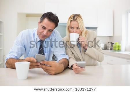 Serious well dressed couple with coffee cups text messaging in the kitchen at home - stock photo