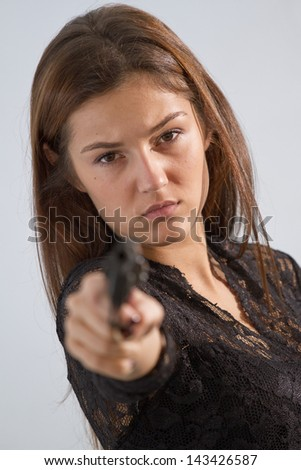 serious woman aiming with a handgun in the camera - stock photo