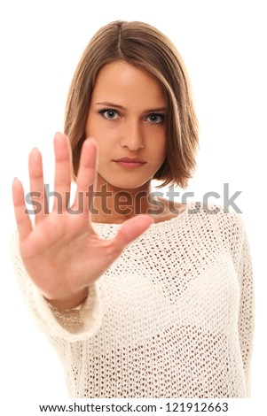Serious woman in sweater showing open palm over a white background - stock photo