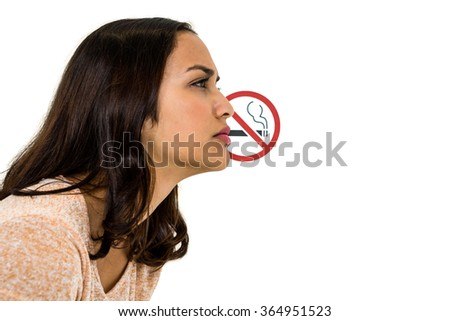 Serious woman looking away with no smoking sign over white background - stock photo