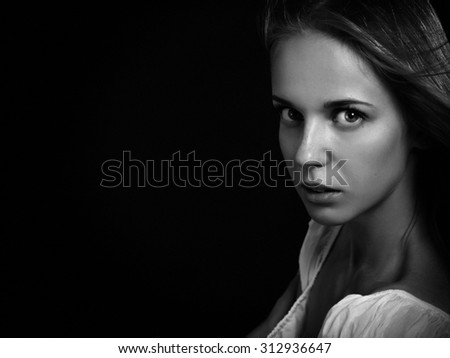 serious woman on black background looking in camera, monochrome - stock photo