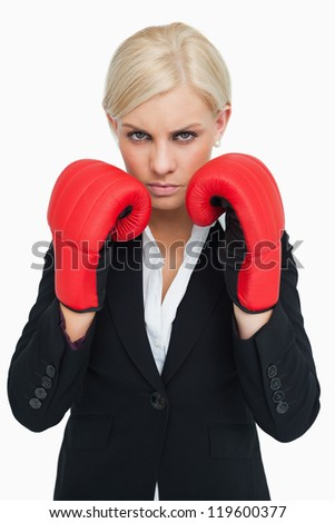Serious woman wearing red gloves against white background - stock photo