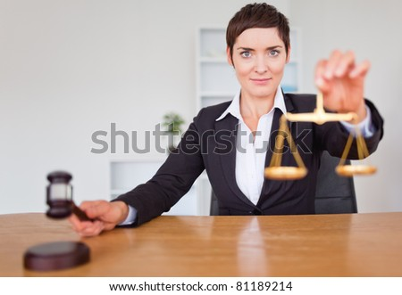Serious woman with a gavel and the justice scale in her office - stock photo