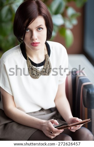 Serious woman with tablet computer sitting in cafe - stock photo