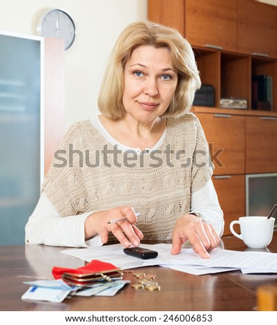 Serious  woman woman working with documents money at  table - stock photo