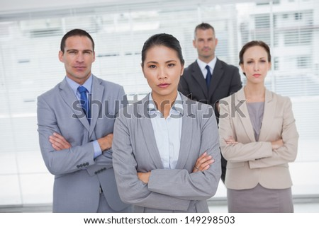 Serious work team posing crossing arms in bright office - stock photo