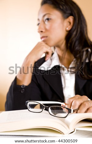 Serious young African-American woman thinking, focus on eyeglasses on book - stock photo