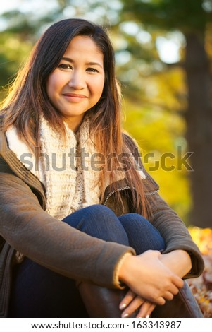 Serious young Asian woman outdoor portrait at the park in autumn - stock photo