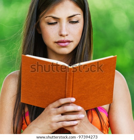 serious young, beautiful girl holding an open book - stock photo