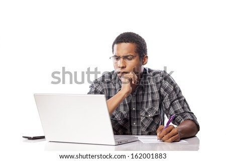 Serious young black man writes data from his laptop - stock photo