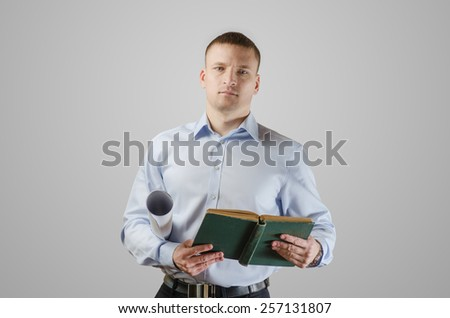 Serious young businessman holding blueprints and architect of the book. On a white background - stock photo