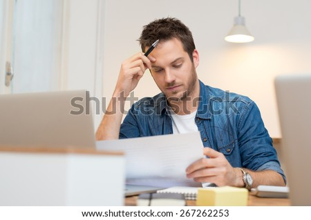 Serious young businessman looking report in office  - stock photo