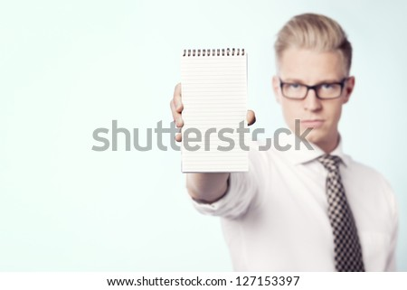 Serious young businessman showing empty notepad with space for text, isolated. - stock photo