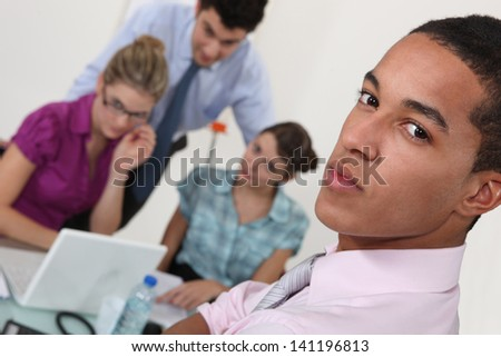 Serious young businessman with colleagues - stock photo