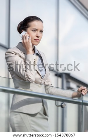 Serious young businesswoman using smart phone at office railing - stock photo