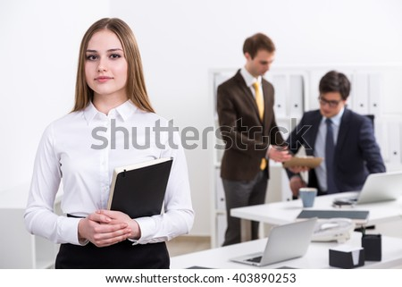 Serious young businesswoman with notebook standing at table, two businessman talking at background. Office. Concept of work. - stock photo