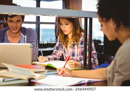 Serious young classmates working together in library - stock photo