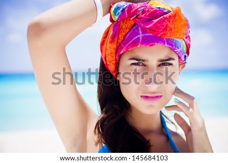 Serious young fashion model posing at the beach with a colorful turban - stock photo