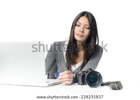 Serious Young female Photographer Transferring Image Files From SD Card to Laptop at her Desk. Isolated on White Background. - stock photo
