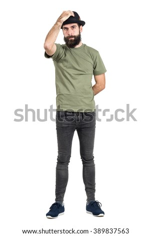 Serious young hipster putting black hat on his head. Full body length portrait isolated over white studio background. - stock photo