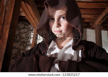 Serious young magician with folded arms hidden in his cloak - stock photo