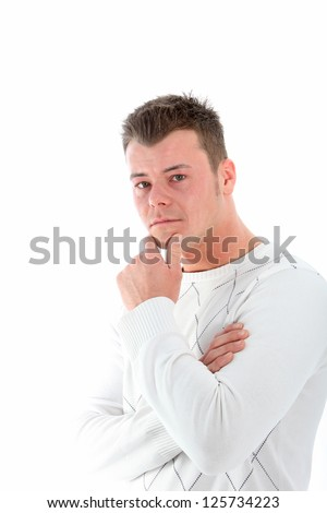 Serious young man deep in thought standing sideways with his hand to his chin looking at the camera isolated on white - stock photo