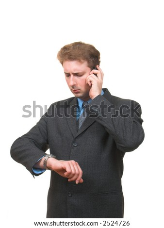 Serious young man in business suit looking at his watch and talking over the mobile phone isolated on white - stock photo