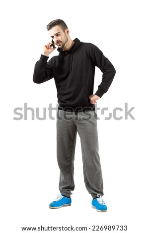 Serious young man in sportswear talking on mobile phone. Full body length isolated over white background. - stock photo
