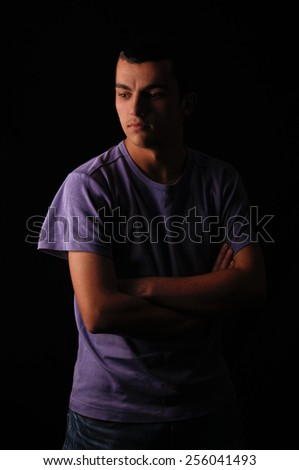 Serious young man standing with arms crossed on black background - stock photo