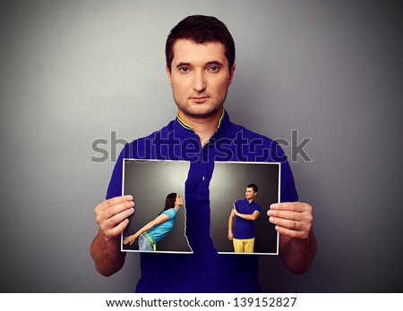 serious young man tearing the photo of couple - stock photo