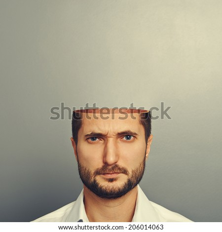 serious young man with open head over grey background - stock photo