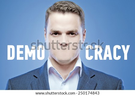 Serious young man without a mouth on a blue background with the words: Democracy - stock photo