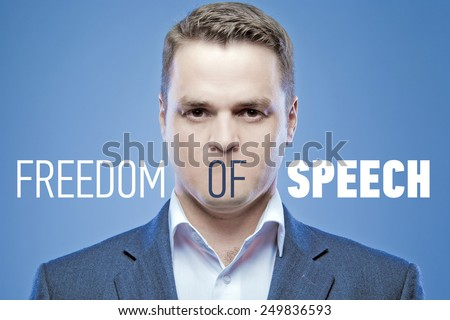 Serious young man without a mouth on a blue background with the words: Freedom of Speech - stock photo