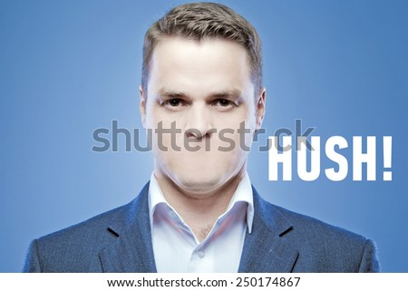 Serious young man without a mouth on a blue background with the words: Hush! - stock photo