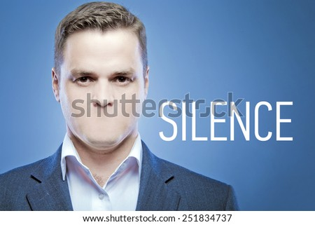 Serious young man without a mouth on a blue background with the words: Silence - stock photo